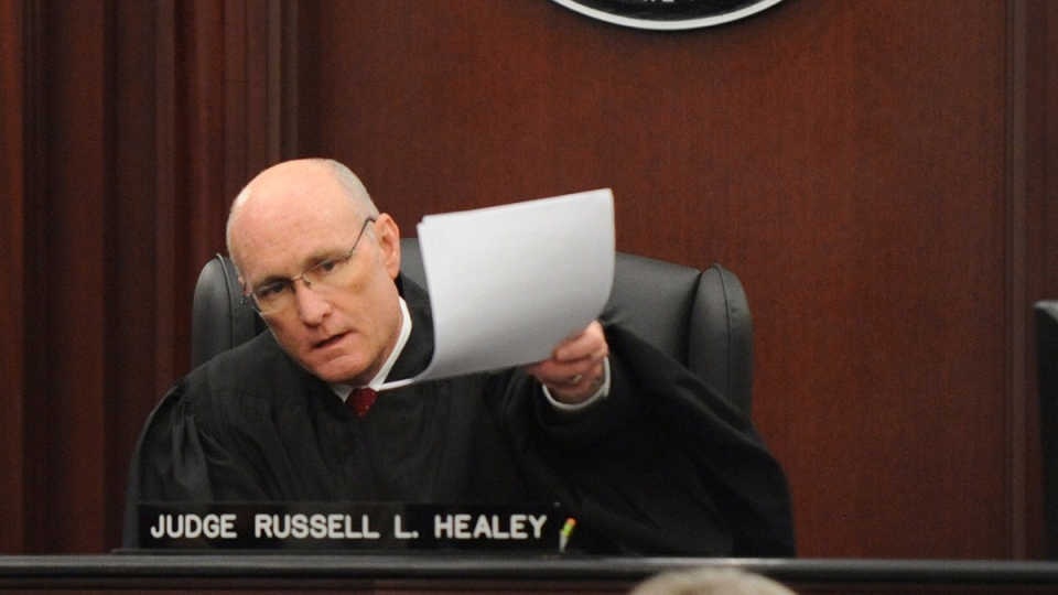 Judge Russell Healey holds up documents as he announces that the jury is deadlocked on charge one and have verdicts in the other four charges while deliberating in the trial of Michael Dunn for the shooting death of Jordan Davis, Saturday Feb. 15, 2014. (The Florida Times-Union, Bob Mack)