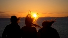 Three girls are silhouetted as their hair blows in the wind while they watch the sunset over the Strait of Georgia from a ferry traveling from Horseshoe Bay, B.C., to Nanaimo, B.C., on Sunday, June 9, 2013. THE CANADIAN PRESS/Jonathan Hayward