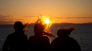 Three girls are silhouetted as their hair blows in the wind while they watch the sunset over the Strait of Georgia from a ferry traveling from Horseshoe Bay, B.C., to Nanaimo, B.C. (THE CANADIAN PRESS/Jonathan Hayward)