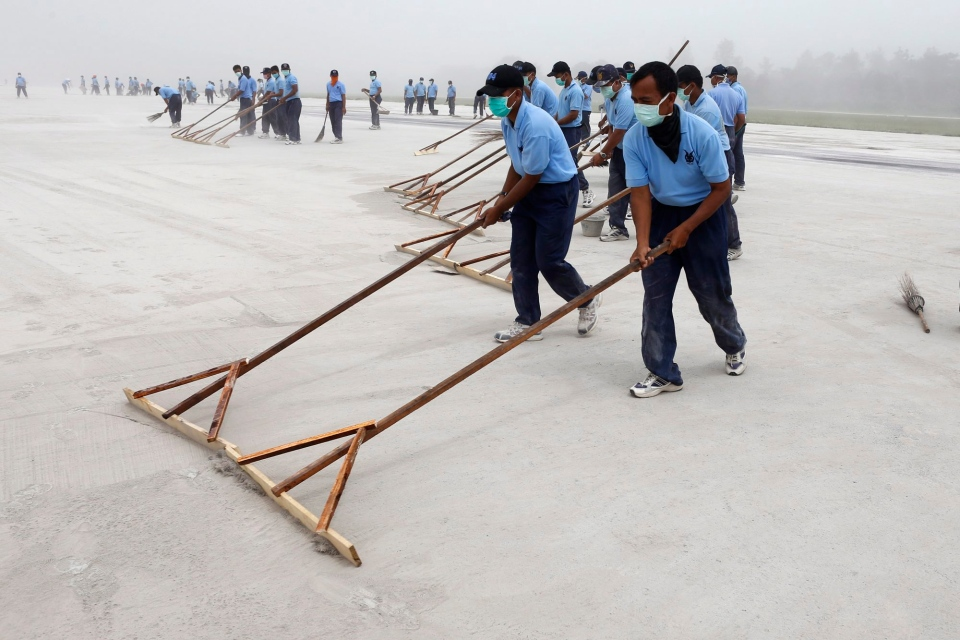 Indonesian air force airmen clean the tarmac which was covered with volcanic ash following an eruption of Mount Kelud at Adisutjipto airport in Yogyakarta, Indonesia, Saturday, Feb. 15, 2014. (AP Photo/A.K Hendratmo)