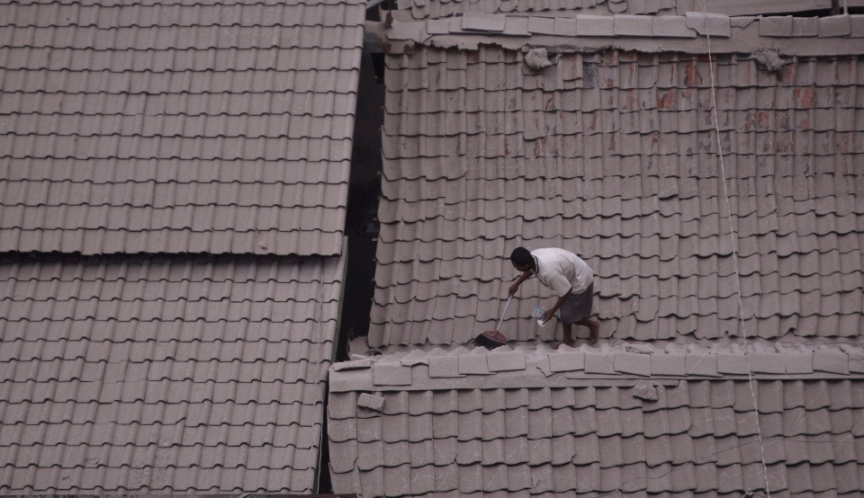 A man cleans volcanic ash-covered rooftop of his house following an eruption of Mount Kelud in Yogyakarta, Indonesia, Saturday, Feb. 15, 2014. (AP Photo/Slamet Riyadi)