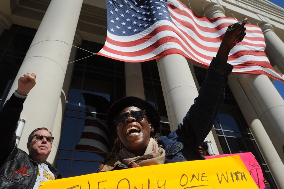 Phyllis Parker chants outside of the Duval County Courthouse as the jury enters the fourth day of deliberations in the trail of Michael Dunn, Saturday, Feb. 15, 2014, in Jacksonville, Fla. (AP Photo/The Florida Times-Union, Kelly Jordan)