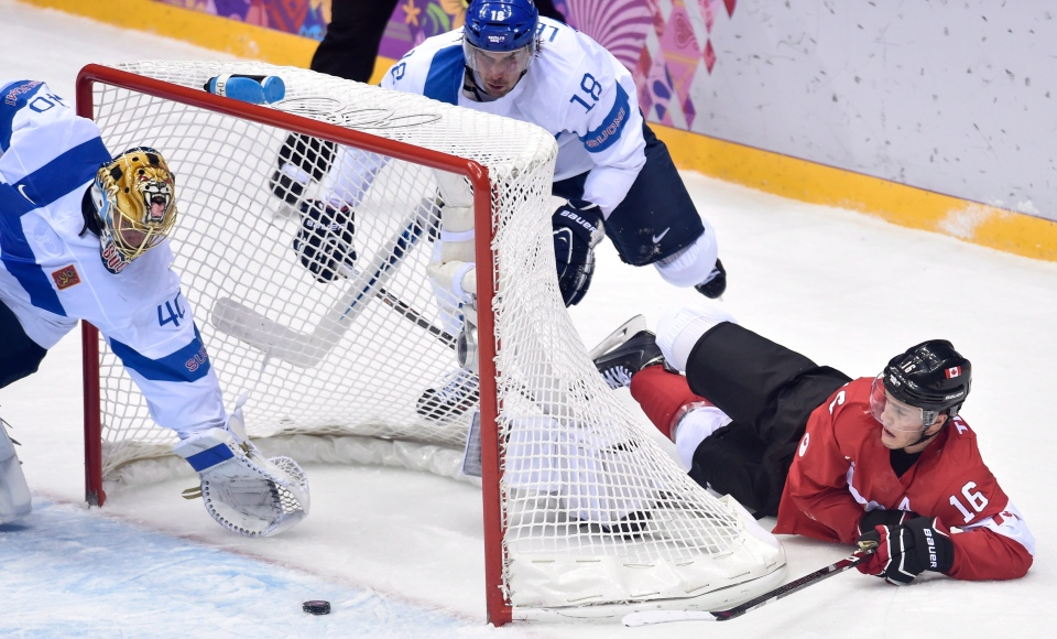 Canada's Jonathan Toews tries for a wraparound goal against Finland goalie Tuukka Rask and Sami Lepisto (centre) during first period preliminary round hockey action at the 2014 Sochi Winter Olympics on Feb. 16, 2014. (Nathan Denette / THE CANADIAN PRESS)