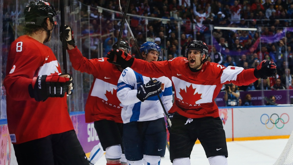 Canada forward John Tavares, right, and forward Jeff Carter, second from left, celebrate with defenseman Drew Doughty (8) after Doughty scored a sudden death overtime goal against Finland during a men's ice hockey game at the 2014 Winter Olympics, in Sochi, Russia, Sunday, Feb. 16, 2014. (AP / Mark Humphrey)