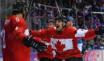 Canada forward John Tavares, right, and forward Jeff Carter, second from left, celebrate with defenseman Drew Doughty (8) after Doughty scored a sudden death overtime goal against Finland during a men's hockey game at the 2014 Winter Olympics, in Sochi, Russia, Sunday, Feb. 16, 2014. (AP / Mark Humphrey)