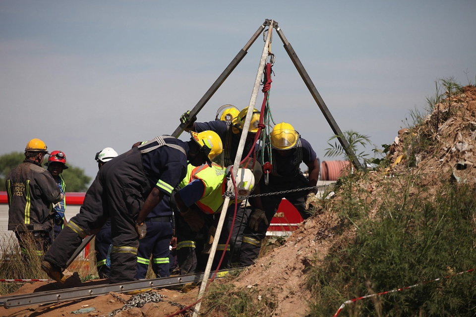 Emergency rescue workers attempt to free trapped illegal miners at a disused gold mine shaft near Benoni, South Africa, Sunday, Feb. 16, 2014. (AP)