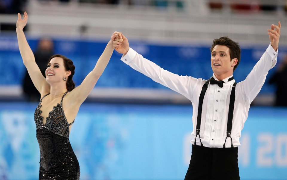 Tessa Virtue and Scott Moir of Canada acknowledge the crowd after finishing their routine in the ice dance short dance figure skating competition at the Iceberg Skating Palace during the 2014 Winter Olympics in Sochi, Russia, Sunday, Feb. 16, 2014. (AP / Darron Cummings)