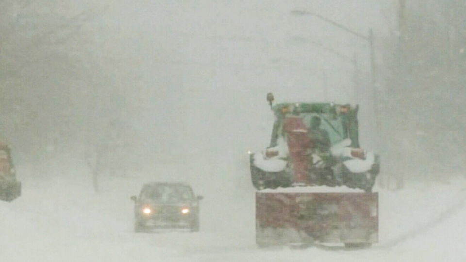 A tractor passes a car as it plows snow off the street during a storm in Moncton, N.B. on Sunday, Feb. 16, 2014.