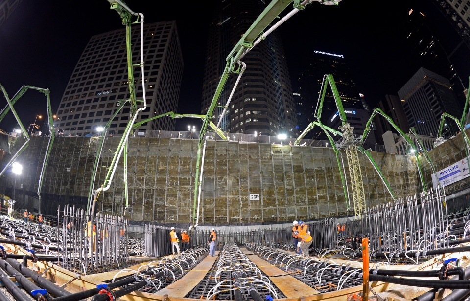 In this photo made with a fisheye lens, crews pour concrete to lay the foundation for the New Wilshire Grand building in a record attempt for the largest continuous concrete pour in history, in downtown Los Angeles, Saturday, Feb. 15, 2014. (AP / Mark J. Terrill)
