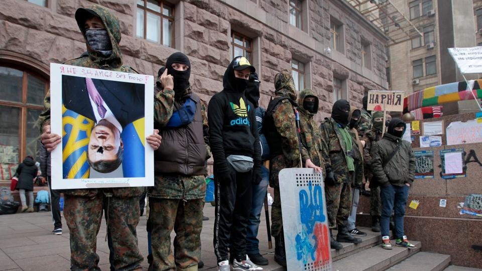 An anti-government activist holds an inverted portrait of President Viktor Yanukovych near City Hall in Kyiv, Ukraine, Sunday, Feb. 16, 2014. (AP / Sergei Chuzavkov)