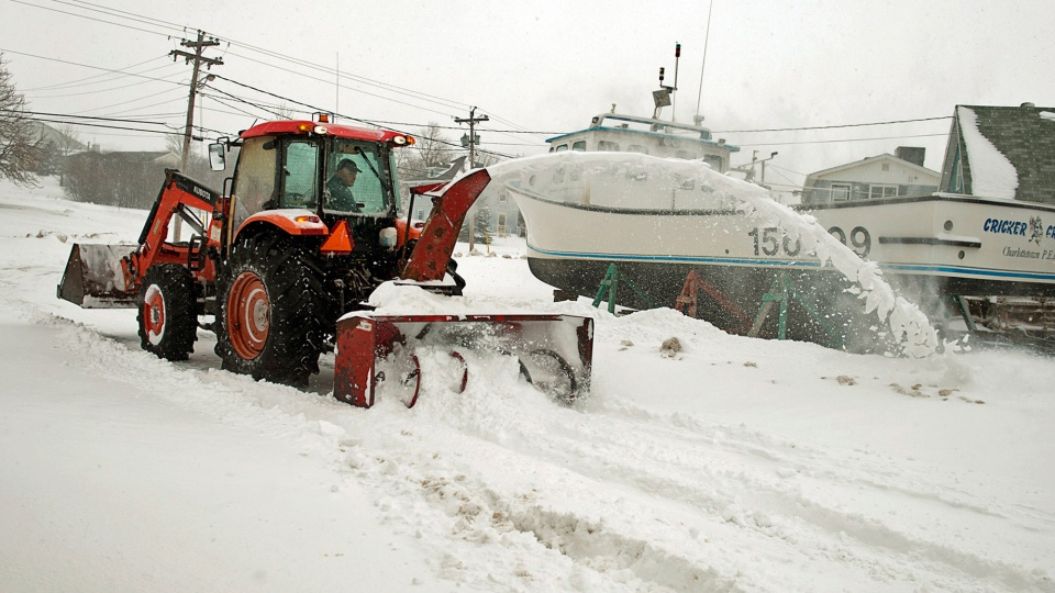 Ronald Toombs clears snow in North Rustico, P.E.I., on Sunday, Feb. 16, 2014. (Andrew Vaughan / THE CANADIAN PRESS)