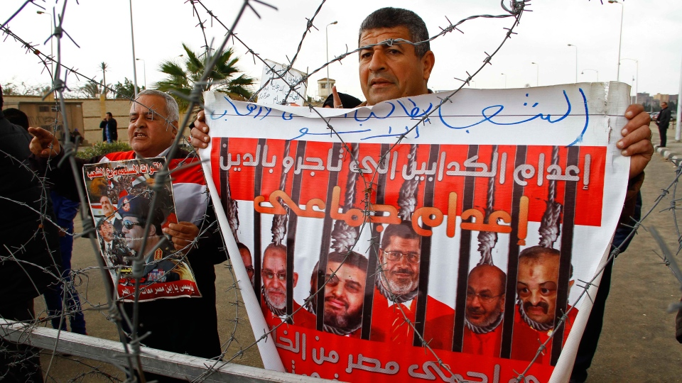 People protest against ousted Egyptian President Mohammed Morsi outside a court where Morsi is facing charges of conspiring with foreign groups and undermining national security in Cairo, Egypt, Sunday, Feb. 16, 2014. (El Shorouk, Ahmed Abdel Fattah)