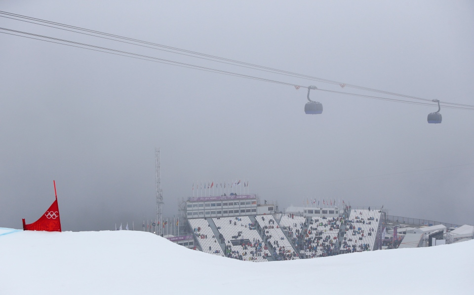 People sit on the tribune after the men's snowboard cross competition was cancelled due to fog at the Rosa Khutor Extreme Park, at the 2014 Winter Olympics, Monday, Feb. 17, 2014, in Krasnaya Polyana, Russia. (AP / Sergei Grits)