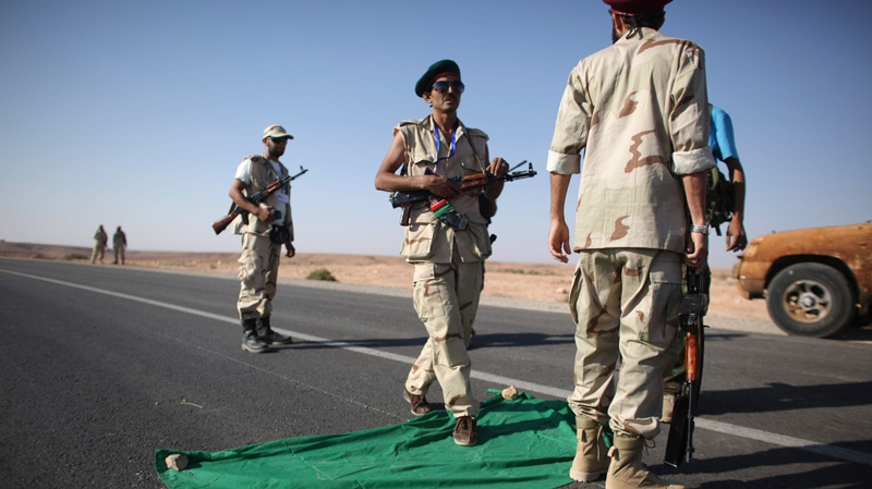 A former rebel fighter steps over a Gadhafi-era flag at a checkpoint at the northern gate of Bani Walid, Libya, Thursday, Sept. 15, 2011. (AP / Alexandre Meneghini)