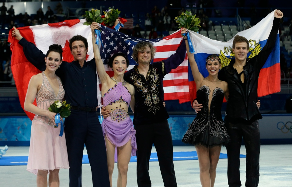 Meryl Davis and Charlie White of the United States, centre, Tessa Virtue and Scott Moir of Canada, left, and Elena Ilinykh and Nikita Katsalapov of Russia posefollowing the flower ceremony for the ice dance free dance figure skating finals at the Iceberg Skating Palace, Monday, Feb. 17, 2014, in Sochi, Russia. (AP / Darron Cummings)