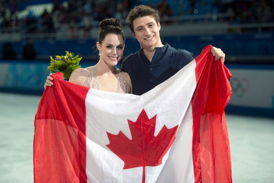 Ice dance silver medallists Canada's Tessa Virtue and Scott Moir pose with the Canadian flag during flowers ceremony at the Sochi Winter Olympics Monday, Feb. 17, 2014 in Sochi. (Paul Chiasson / THE CANADIAN PRESS)