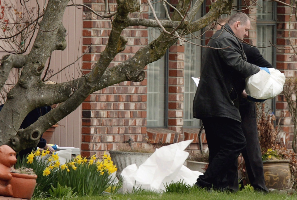 A B.C. Coroner carries the body of a newborn baby after it was found dead in a plastic bag between two homes in Vancouver, B.C., on April 2, 2009. (Darryl Dyck / THE CANADIAN PRESS)