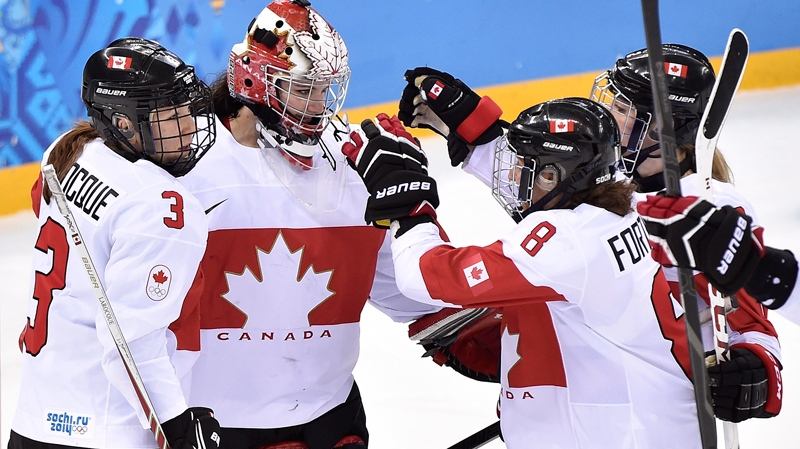 Canada goalie Shannon Szabados centre, celebrates with teammates Jocelyne Larocque (3) and Laura Fortino (8) after defeating Switzerland 3-1 in semifinal women's Olympic hockey action at the 2014 Sochi Winter Olympics in Sochi, Russia on Monday, February 17, 2014. (THE CANADIAN PRESS/Nathan Denette)