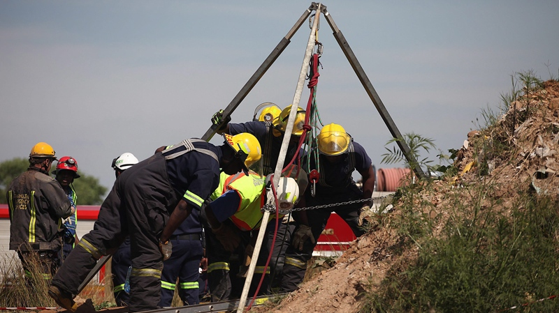 Emergency rescue workers attempt to free trapped illegal miners at a disused gold mine shaft near, Benoni, South Africa, Sunday, Feb. 16, 2014. (AP Photo)