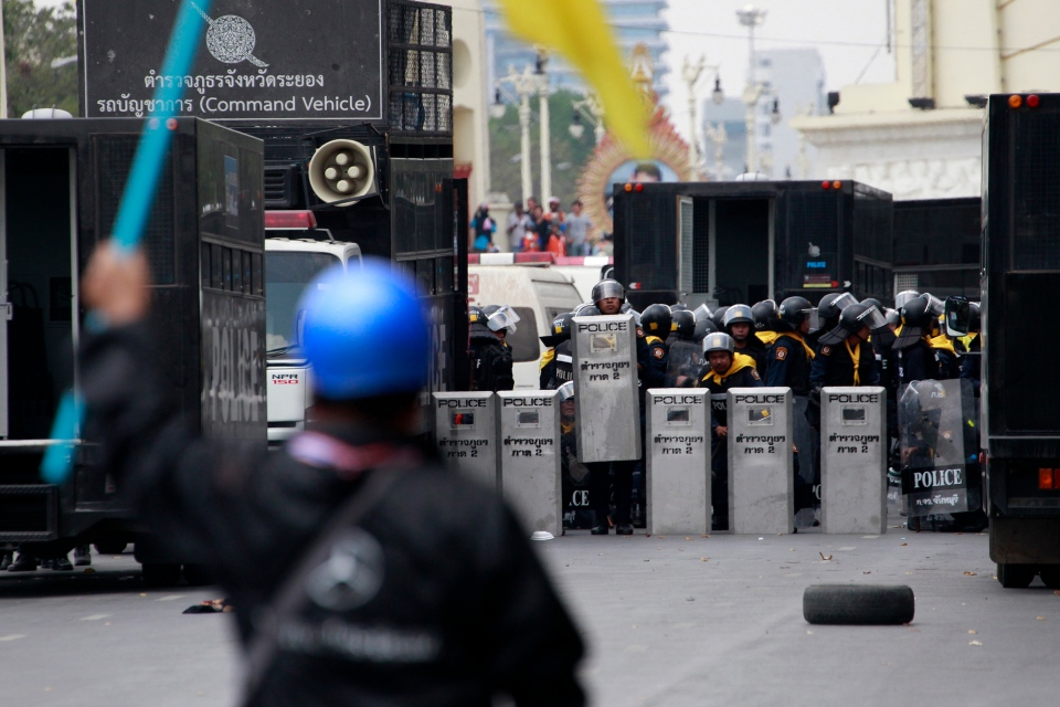 A Thai protester confronts police officers prior to a clash between police force and anti-government protesters near democracy monument, background in Bangkok, Thailand, Tuesday, Feb. 18, 2014. (AP / Wason Wanichakorn)
