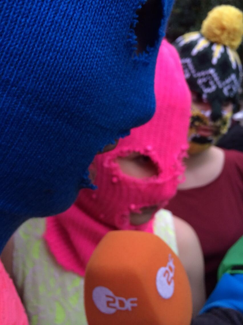 Pussy riot members Nadezhda Tolokonnikova, wearing a blue mask, and Maria Alekhina (pink) speak with reporters following their release on Tuesday, Feb. 18, 2014. (Joy Malbon/CTV News)