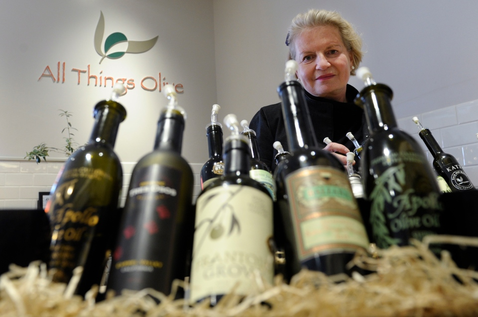 This photo shows California Olive Oil Council Executive Director Patricia Darragh posing with a collection of California olive oil at the All Things Olive shop in Washington on Feb. 12, 2014. (AP / Susan Walsh)