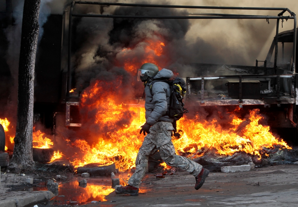 An anti-government protester runs in front of a flaming barricade during clashes with riot police outside Ukraine's parliament in Kyiv, Ukraine, Tuesday, Feb. 18, 2014. (AP / Sergei Chuzavkov)
