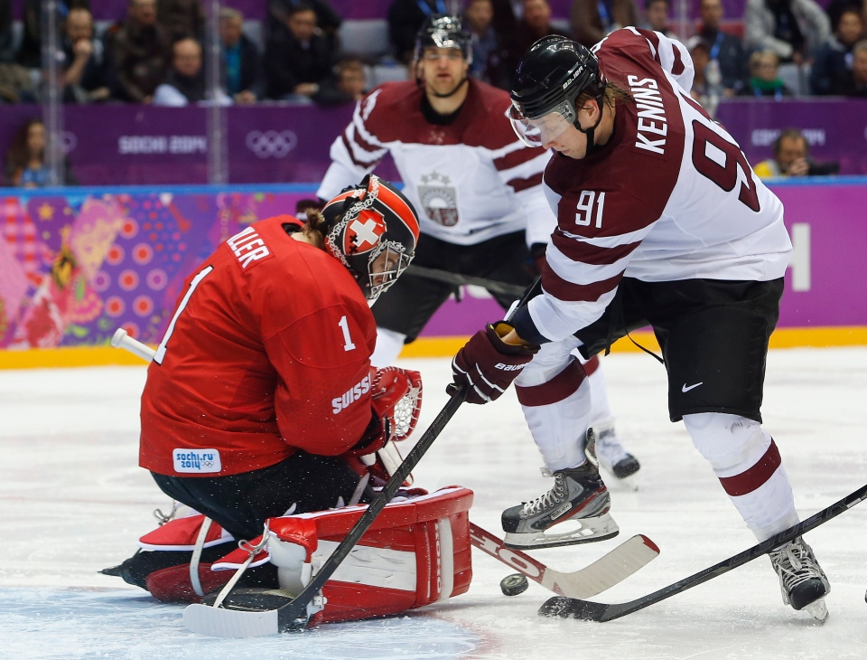 Latvia forward Ronalds Kenins, right, tries to score against Switzerland goaltender Jonas Hiller in the third period of a men's ice hockey game at the 2014 Winter Olympics, Tuesday, Feb. 18, 2014, in Sochi, Russia. (AP / Mark Humphrey)