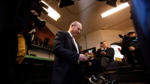 B.C. Finance Minister Mike de Jong pays for having the soles replaced on his budget day shoes after at the Olde Towne Shoe Repair in Victoria, B.C. Monday, Feb. 17, 2014. (Chad Hipolito / THE CANADIAN PRESS)