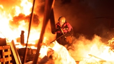 Anti-government protesters runs through Kyiv fire