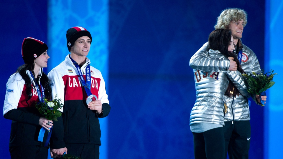 Canadians Tessa Virtue and Scott Moir, left, look on with their silver medals as United States Meryl Davis and Charlie White, right, celebrate their gold medal for ice dancing at the medal ceremony during the 2014 Sochi Winter Olympics in Sochi, Russia on Tuesday, Feb. 18, 2014. (Nathan Denette / THE CANADIAN PRESS)