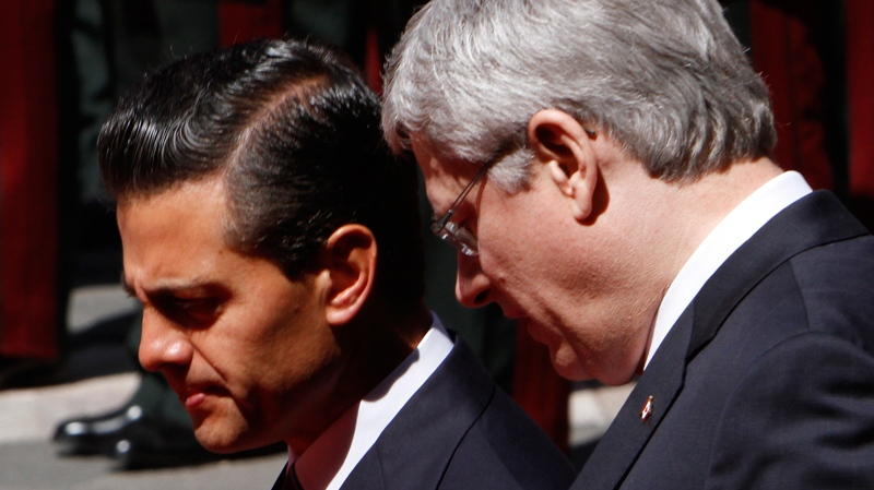 Mexican President Enrique Pena Nieto, left, and Prime Minister Stephen Harper talk at the National Palace in Mexico City, Tuesday, Feb. 18, 2014. (AP / Marco Ugarte)