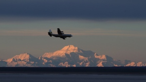 Mount McKinley provides a backdrop to a cargo plane approaching Ted Stevens Anchorage International Airport on Monday, Nov. 4, 2013, in a view from Kincaid Park in Anchorage, Alaska. (AP Photo/Dan Joling)