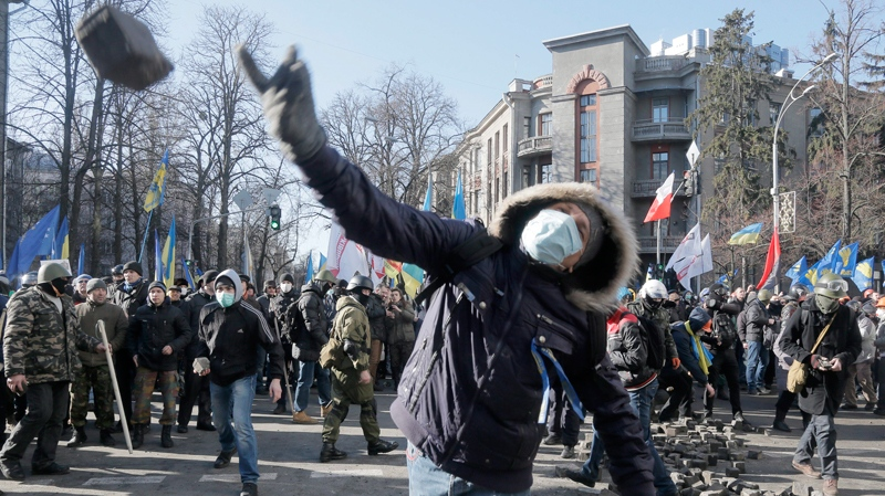 An anti-government protester throw a stone during clashes with riot police outside Ukraine's parliament in Kyiv, Ukraine, Tuesday, Feb. 18, 2014. (AP Photo/Efrem Lukatsky)