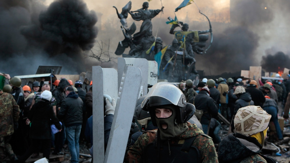 Anti-government protesters protected themselves with shields during clashes with riot police in Kyiv's Independence Square, the epicenter of the country's current unrest, Kyiv, Ukraine, Wednesday, Feb. 19, 2014. (AP / Sergei Chuzavkov)