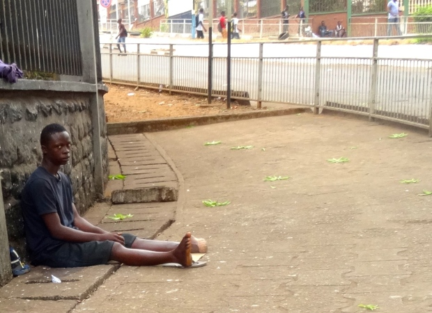 A man who is missing his left foot begs near the capital building in downtown Freetown. (Ethan Faber/CTV News)