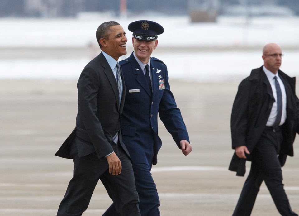 U.S. President Barack Obama laughs as he is escorted by Air Force Col. Daniel Waters, vice-commander of Andrews Air Force Base, as he walks to board Air Force One for a day trip to Mexico to work on issues of trade and other neighbor-to-neighbor interests with the leaders of Mexico and Canada at Andrews Air Force Base, Md., Wednesday, Feb. 19, 2014. (AP / J. Scott Applewhite)