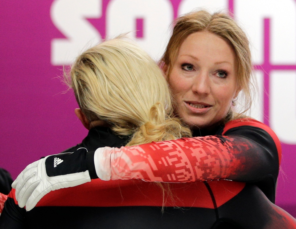 The team from Canada CAN-1, piloted Kaillie Humphries with brakeman Heather Moyse, hug during the women's bobsled competition at the 2014 Winter Olympics, Wednesday, Feb. 19, 2014, in Krasnaya Polyana, Russia. (AP / Natacha Pisarenko)