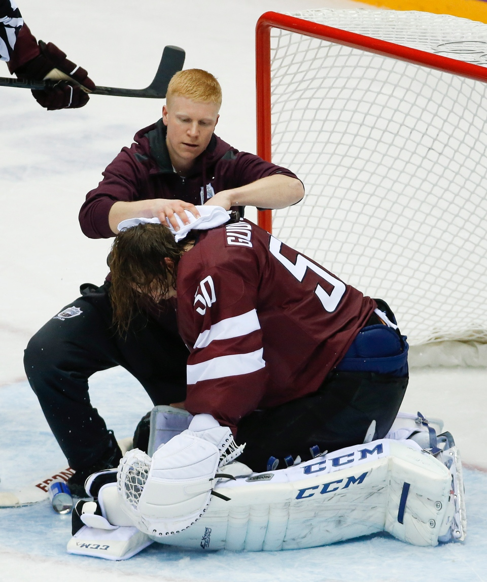 A trainer treats Latvia goaltender Kristers Gudlevskis after a collision with a Canadian player during the third period of a men's quarterfinal ice hockey game at the 2014 Winter Olympics, Wednesday, Feb. 19, 2014, in Sochi, Russia. (AP / Mark Humphrey)