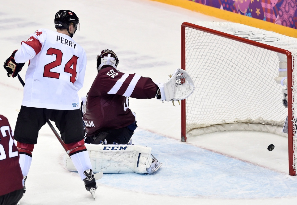 Canada forward Corey Perry watches Canada's defenceman Shea Weber winning goal goes past Latvia goalie Kristers Gudlevskis, right, during third period quarter-final hockey action at the 2014 Sochi Winter Olympics in Sochi, Russia on Wednesday, Feb. 19, 2014. (Nathan Denette / THE CANADIAN PRESS)