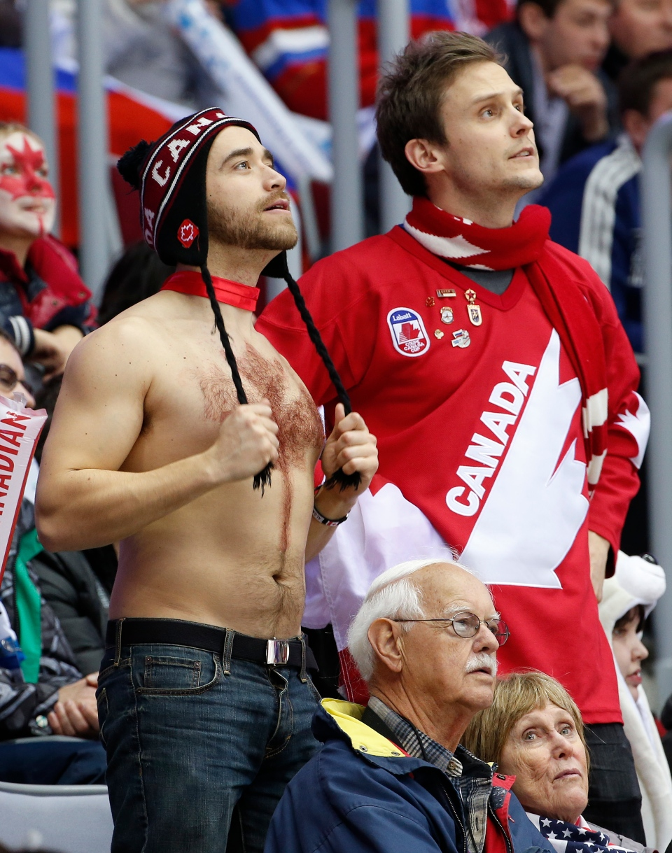 Canadian hockey fans anxiously wait for a call during Canada Latvia game at the 2014 Winter Olympics, Wednesday, Feb. 19, 2014, in Sochi, Russia. (AP / Julio Cortez)