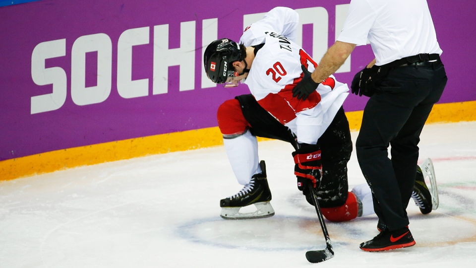 Canada forward John Tavares is helped up off the ice by a trainer during the second period of a men's quarterfinal ice hockey game against Latvia at the 2014 Winter Olympics in Sochi, Russia, Wednesday, Feb. 19, 2014. (AP / Mark Humphrey)