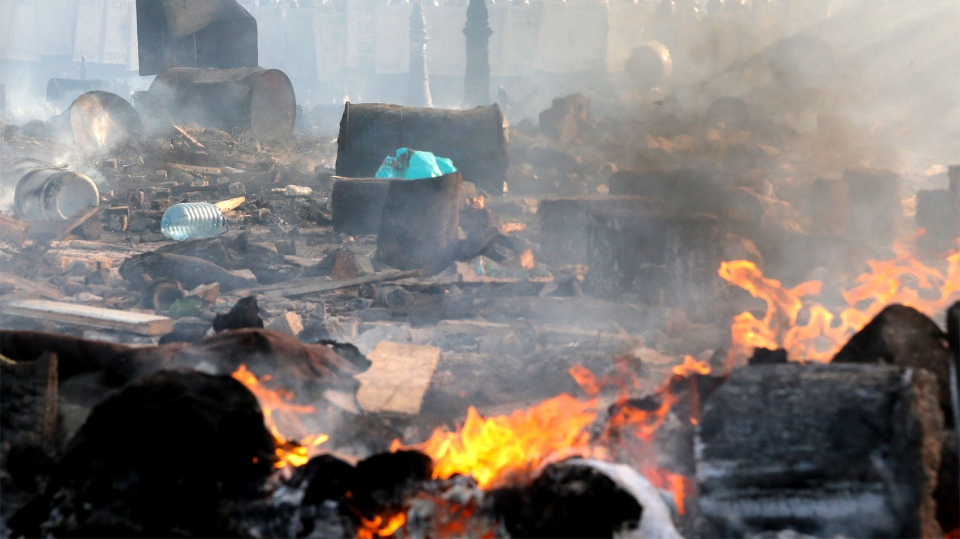 A battle scene is covered with flame and smoke while riot police stand in the background during clashes with protesters in Kiev's Independence Square, the epicenter of the country's current unrest, Kiev, Ukraine, Wednesday, Feb. 19, 2014. (AP / Efrem Lukatsky)