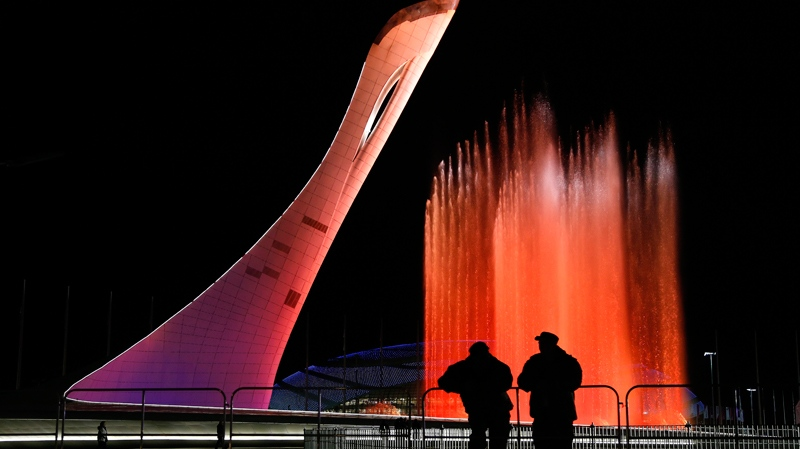 Security personnel watch a practice run of a fountain show to music from 'Swan Lake' on the perimeter of the Olympic cauldron in preparation for the 2014 Winter Olympics, Thursday, Feb. 6, 2014, in Sochi, Russia. (AP Photo/Julie Jacobson)
