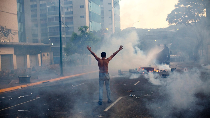 A demonstrator raises his arms toward the Bolivarian National Police (BNP) firing tear gas and a water canon in the Altamira neighborhood of Caracas, Venezuela, Wednesday, Feb. 19, 2014. (AP Photo/Rodrigo Abd)