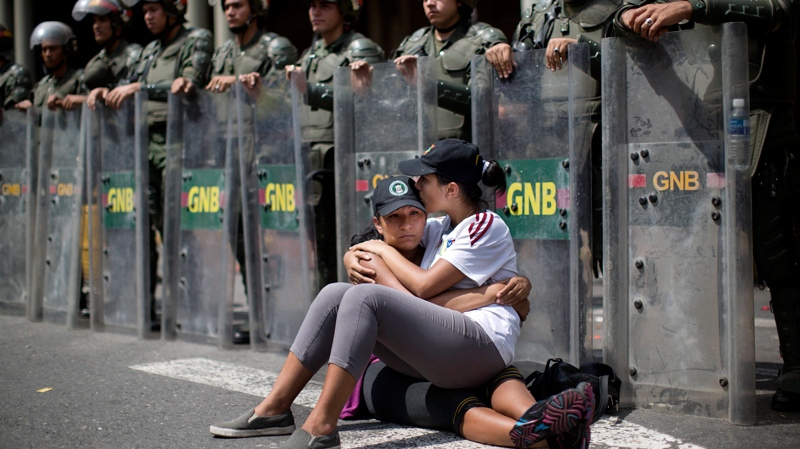 Women embrace as they sit in front of a line of National Bolivarian Guard outside the Palace of Justice court in Caracas, Venezuela, Wednesday, Feb. 19, 2014. (AP Photo/Rodrigo Abd)