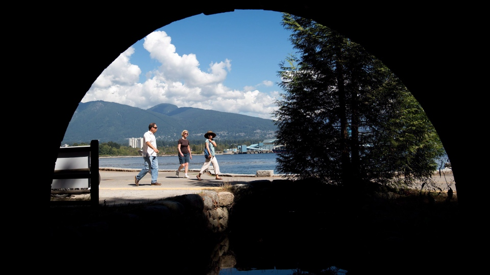 In this file photo, pedestrians are framed underneath a vehicle bridge while walking along the Stanley Park seawall in Vancouver, B.C., on Sunday, August 25, 2013. THE CANADIAN PRESS/Darryl Dyck