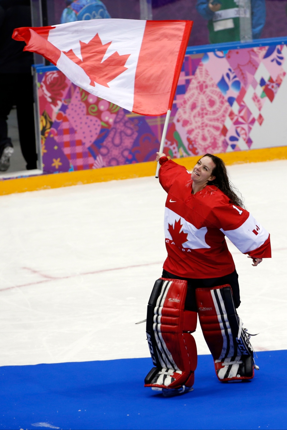 Goalkeeper Shannon Szabados of Canada (1) wave a flag after the women's gold medal ice hockey game against USA at the 2014 Winter Olympics in Sochi, Russia, Thursday, Feb. 20, 2014. (AP / Petr David Josek)