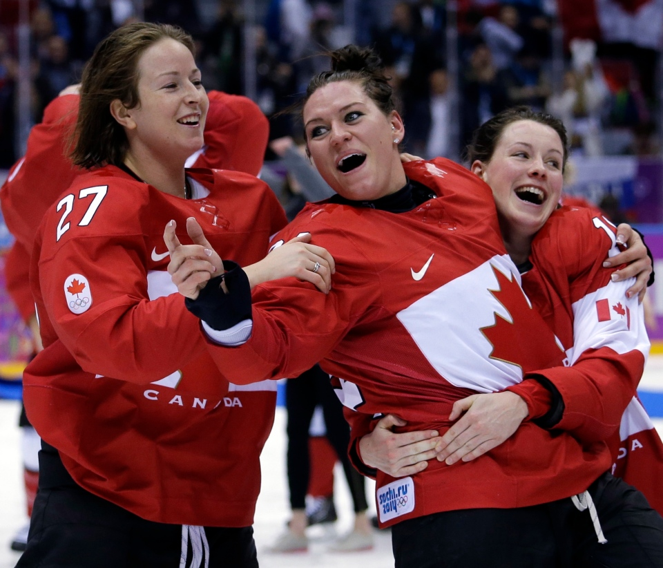 Canada's Tara Watchorn (27), Natalie Spooner (24) and Catherine Ward (18) celebrate after beating the U.S.A. 3-2 in overtime of the gold medal women's ice hockey game at the 2014 Winter Olympics in Sochi, Russia, Thursday, February 20, 2014. (AP / David Goldman)