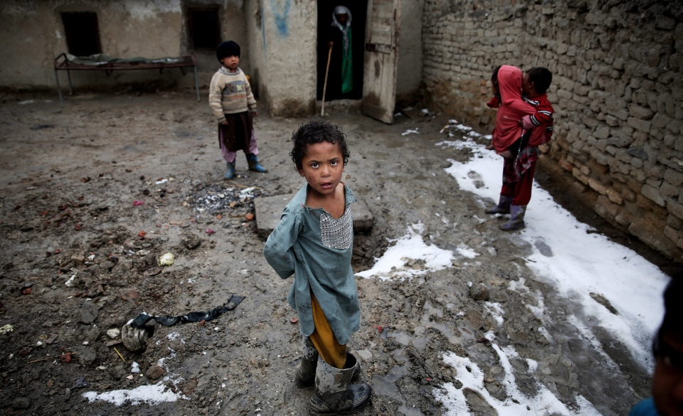 Afghan internally displaced children stand in a muddy yard at a poor neighborhood in Kabul, Afghanistan, Wednesday, Feb. 19, 2014. (AP / Massoud Hossaini)
